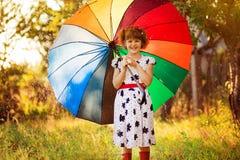Promenade heureuse de fille d'enfant avec le parapluie multicolore sous la pluie photos libres de droits