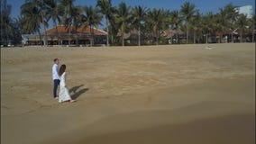 Promenade heureuse de jeunes mariés le long de plage large de sable banque de vidéos