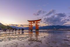 Promenade laissée à la grande Torii porte de flottement rouge d'Itsukushima image stock