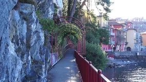 Promenade of Lake Como with plants on red archways and railings. Varenna, Italy stock footage