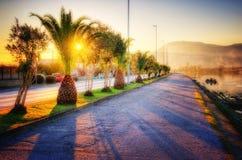 Promenade langs de rivierbank bij warme zonsondergang Stock Fotografie
