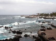 The promenade and lido at puerto de la cruz in tenerife with people on the seafront and dramatic waves breaking over the rocks Stock Photo