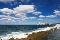 Promenade of the Malecon of Havana, Morro Castle and its lightho. The Promenade of the Malecon of Havana, Morro Castle and its lighthouse with crashing waves Royalty Free Stock Images