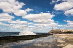 Promenade of the Malecon of Havana, Morro Castle and its lightho. The Promenade of the Malecon of Havana, Morro Castle and its lighthouse with crashing waves Royalty Free Stock Photography