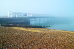 Promenade in the mist. Pier in the fog going into the sea, with sun coming through, by the pebble beach on English coast stock images