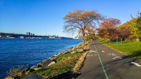 Promenade next to the Hudson River, looking northward toward the George Washington Bridge, on a colorful autumn royalty free stock images