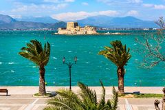 Bourtzi fortress, Nafplio, Greece. Promenade with palm trees and Bourtzi fortress in the sea in Nafplio or Nafplion, Greece, Peloponnese stock images