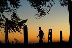 Promenade par la silhouette d'homme de coucher du soleil images stock