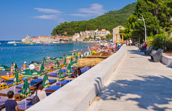 The promenade. PETROVAC, MONTENEGRO - JULY 16, 2014: The cozy promenade with the view on the old town with the ruins of the medieval ramparts, on July 16 in Stock Photo