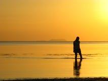 Promenade rêveuse de plage au coucher du soleil Images stock