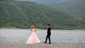 Promenade romantique des jeunes mariés près de la grande rivière et des montagnes pittoresques Jour du mariage banque de vidéos