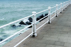 Ocean. Sea or ocean waves and rocks over stone dales and white deco pillars promenade Stock Image