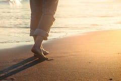 Promenade sur la plage au coucher du soleil Image stock
