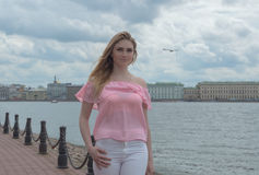 The promenade walks an attractive girl in a pink blouse. Stock Photography
