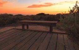 Promenadebank bij Crystal Cove-strand bij zonsondergang stock afbeelding