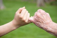 Promesse aînée et jeune de mains Image stock