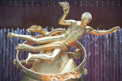 Prometheus Statue at Rockefeller Center, New York. A close-up view of the hand of the golden sculpture of the Greek god Prometheus holding the Gift of Fire. over Royalty Free Stock Photos