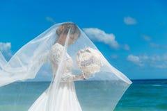 Prometido moreno hermoso en el vestido de boda blanco con largo grande Fotografía de archivo