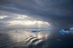 Promienia słońca szuja przez chmury, odbija na wodzie z górami lodowa Zdjęcia Royalty Free