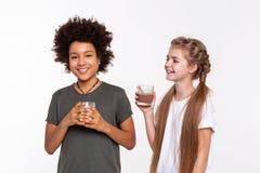 Promieniejący pozytywni dzieci ma rozmowę podczas gdy pijący obrazy royalty free
