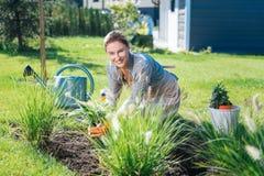 Promieniejąca interesująca kobieta cieszy się jej weekend podczas gdy kwietnikowe rośliny zdjęcie royalty free