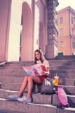 Promieniejąca młoda kobieta cieszy się jej weekend z magazynem i lato koktajlem zdjęcie royalty free