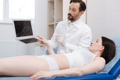 Prominent advanced doctor showing possible result of the procedure Royalty Free Stock Photo