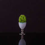 Prominent egg cup with elegante posh green Easter egg Stock Photo