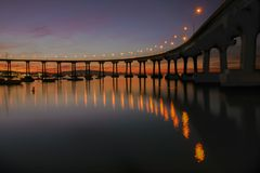 The promise of a great day. Before sunrise, a view of Coronado bridge during early spring morning. Sleeping sailing boats on bay Royalty Free Stock Images