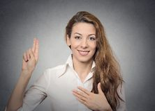 Promise hand gesture. Young happy woman showing promise hand gesture on grey wall background Royalty Free Stock Images