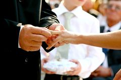 Promise Ring. A groom putting a wedding ring on his brides finger Royalty Free Stock Photography