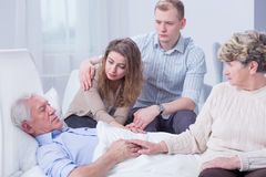 Promise us you'll be fine. Shot of a sick senior men surrounded by his family supporting him Stock Image