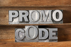 Promo code tray. Promo code phrase made from metallic letterpress type on wooden tray royalty free stock images