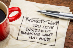 Promote what you love on napkin. Promote what you love instead of bashing what you hate - handwriting on a napkin with cup of coffee Stock Photo