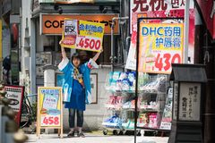 Promoters with billboards. Cosmeceuticals shop on the streets of Kyoto, Japan, June 2016 stock photos