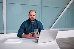 Promoteur masculin posant avec le téléphone portable après avoir travaillé au filet-livre tout en se reposant dans l'intérieur mo Images stock