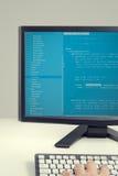 Promoteur travaillant sur des codes sources sur l'ordinateur au bureau Image libre de droits