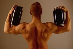 Promoting proper body functioning. Strong man hold supplement bottles. Eat a healthy diet. Muscular man with vitamin. Supplements. Bodybuilding sport and stock images
