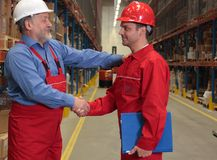 Promotion - congratulations. Two workers in uniforms in warehouse.One is older, one is younger.Warm,sincere handshake on promotion royalty free stock photography