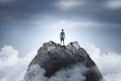 Promotion and leader concept. Businessman standing on abstract mountain on sky background. Promotion and leader concept stock image