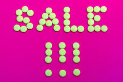 Promotional sign dressed with yellow candies on a pink backgroun Stock Image