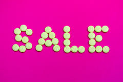 Promotional sign dressed with yellow candies on a pink backgroun Royalty Free Stock Photography