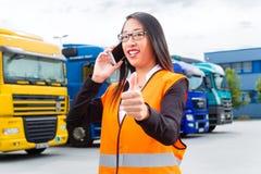 Promotor femenino delante de los camiones en un depósito Fotografía de archivo