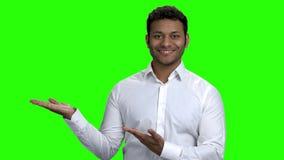 Promotor indio que presenta algo en la pantalla verde almacen de video