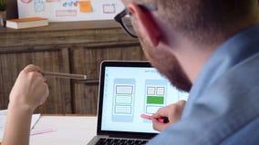 Promotores móviles del app que discuten el prototipo móvil del app en la pantalla de ordenador almacen de metraje de vídeo