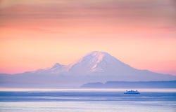 Promu skrzyżowanie Puget Sound przy wschodem słońca z górą Dżdżysty i Zdjęcia Royalty Free