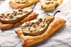 Päron bakade i smördeg med gorgonzola ost och valnötter Arkivbild