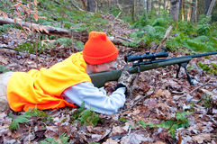 Prone woman hunter. A woman hunter likes in prone position with her rifle propped on a bipod. She is wearing hunter's orange, and it is autumn Stock Photography