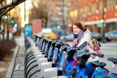 Pronto turistico della giovane donna felice a guidare una bicicletta locativa in New York al giorno di molla soleggiato Viaggiato fotografia stock