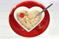 燕麦粥或Proodge早餐在hstrawberry心脏碗的机智 免版税库存照片